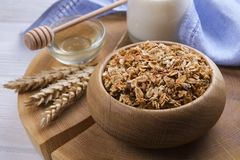 A wooden bowl of trail mix with almonds, raisins, seeds, cashew, hazelnut nuts, glass of milk and honey on white table. Vegetarian. Dietary sports nutrition Royalty Free Stock Image