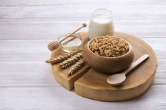 A wooden bowl of trail mix with almonds, raisins, seeds, cashew, hazelnut nuts, glass of milk and honey on white table. Vegetarian. Dietary sports nutrition Stock Photo