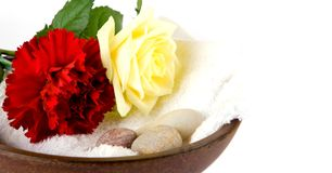 Wooden bowl with white towel and scattered pebbles. Decorated with a white rose and red carnation, suitable for spa and healthcare setting Stock Photography