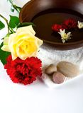 Wooden bowl with white towel and scattered pebbles. Decorated with a white rose and scarlet carnation, suitable for spa and healthcare setting Stock Photography