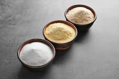 Wooden bowls with different types of flour. On gray background Stock Photography