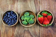 Wooden Bowls Filled With Healthy Fresh Fruit on a Rustic Wooden Background stock photos