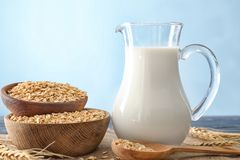 Wooden bowls with oatmeal flakes and pitcher of milk Royalty Free Stock Photos