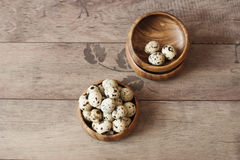 Wooden bowls with quail eggs. Rustic wood background, diffused natural light. A different type of concept image for Easter Royalty Free Stock Image
