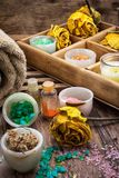 Wooden box with accessories for Spa treatments. Sea aromatic salt for Spa treatments on the background of yellow rose buds Stock Image
