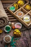 Wooden box with accessories for Spa treatments. Sea aromatic salt for Spa treatments on the background of yellow rose buds Royalty Free Stock Image
