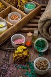 Wooden box with accessories for Spa treatments. Sea aromatic salt for Spa treatments on the background of yellow rose buds Stock Photography