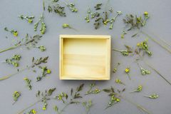 A wooden box against the background of wild flowers. An empty place for an object or text. Gray background royalty free stock photo