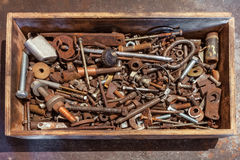 The wooden box with bolts, screws, nuts, bearings, valves, washers, nails on the metal background Royalty Free Stock Photos