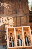 A wooden box with a bottle of wine and barrel. A wooden box with a bottle of wine and a wine barrel royalty free stock photo