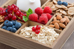 Wooden box with breakfast items - oatmeal, granola, nuts, berry. Wooden box with breakfast items - oatmeal, granola, nuts, berries and milk, close-up, horizontal Royalty Free Stock Photography