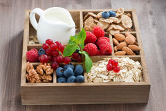 Wooden box with breakfast items - oatmeal, granola, nuts, berry. Wooden box with breakfast items - oatmeal, granola, nuts, berries and milk on table Stock Image