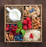 Wooden box with breakfast items - oatmeal, granola, nuts, berry. Wooden box with breakfast items - oatmeal, granola, nuts, berries and milk, top view, close-up Stock Photos