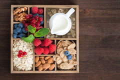 Wooden box with breakfast items - oatmeal, granola, nuts, berry. Wooden box with breakfast items - oatmeal, granola, nuts, berries and milk, top view, horizontal Royalty Free Stock Images