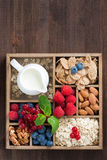 Wooden box with breakfast items - oatmeal, granola, nuts, berry. Wooden box with breakfast items - oatmeal, granola, nuts, berries and milk, top view, vertical Stock Images