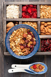 Wooden box with breakfast items - oats, granola muesli, nuts, honey, dried berries and milk. Top view. Royalty Free Stock Photo