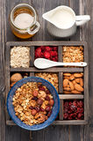 Wooden box with breakfast items - oats, granola muesli, nuts, honey, dried berries and milk. Top view. Royalty Free Stock Images