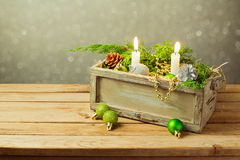 Wooden box with Christmas decorations and candles over dreamy background. Christmas table composition royalty free stock photos