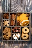 Wooden box with Christmas sweets and spices on wooden background. Top view stock image