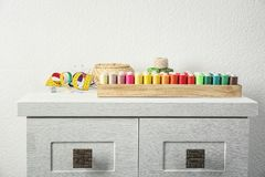 Wooden box with color sewing threads. On cabinet Royalty Free Stock Photo