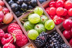 Wooden box with colorful berries. Close-up.  stock photo
