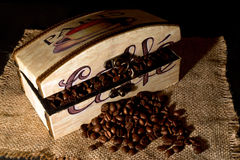 Wooden box filled with coffee beans on jute cloth Royalty Free Stock Photos