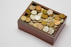 Wooden box filled with various coins Royalty Free Stock Images