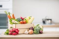 Wooden box full of fresh healthy vegetables. Broccoli carrot radish onion garlic corn on wooden kitchen table royalty free stock image