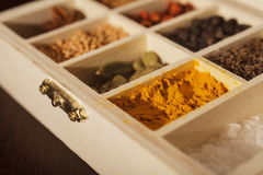 Wooden box full of spices. Closeup of a wooden box with sections full of colorful spices. Focus is on turmeric. Dark wooden background Stock Photo