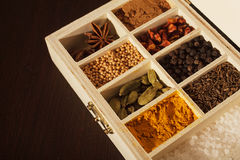 Wooden box full of spices. Closeup of a wooden box with sections full of colorful spices. Focus is on turmeric. Dark wooden background Royalty Free Stock Photography