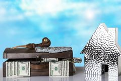 Wooden box full with US 100 dollars and a metallic house on tabl stock photo