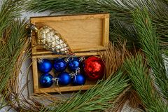 Open brown wooden box with Christmas toys and a pine cone in pine branches. Wooden box with a glass bush and Christmas toys stock photography