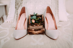 Wooden box with gold wedding rings and flowers stand next to elegant bridal shoes. Rustic wooden box with gold wedding rings and flowers stand next to elegant Royalty Free Stock Images