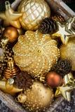 Wooden box with golden Christmas decorations, top view, closeup Stock Photos