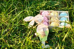 Wooden box with hand painted pink, yellow and blue eggs lies on spring green grass at sunlight. Happy Easter! Decoration, egg hunt royalty free stock photos
