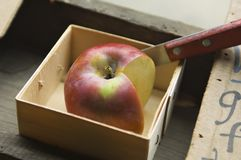 Apple and knife in a wooden box for produce sampling. A wooden box holds a knife and a red apple that has been quartered for sampling at an apple farm royalty free stock photos