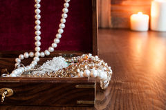 Wooden box of jewels and jewelry on a background of burning candles Royalty Free Stock Photos