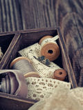 Wooden box with laces, ribbons and threads Stock Photo