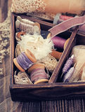 Wooden box with laces, ribbons and threads Royalty Free Stock Photos