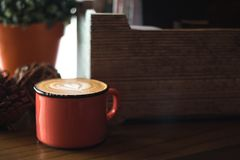 Wooden box and latte in a red mug stock image