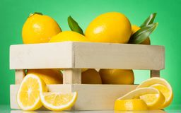 Wooden box with lemons, near slices and rind of citrus fruits on green. Background stock photo