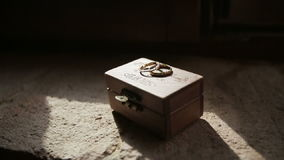 Wooden box with luxury wedding rings in the dark room stock footage