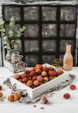 Wooden box with lychees. On white table stock image