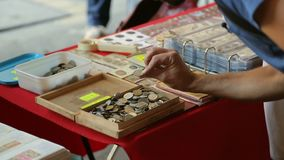 Wooden box with many ancient coins on table, male tourist choosing souvenir. Stock footage stock footage