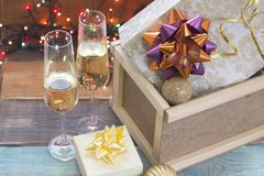 A wooden box with ornaments and gifts and two glasses of champagne. A romantic Christmas evening for a couple. Two glasses of champagne, a beige gift box with a Stock Photos