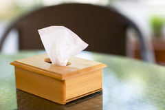 Wooden box with paper napkins on the table. The napkin holder is on a glass table Stock Images