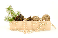 Wooden box with pine branch, cones and decorations. Wooden box with rope handle filled with pine cones, straw balls, green pine branch and gold beads. Isolated Stock Photos