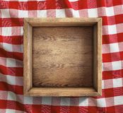 Wooden box on red picnic tablecloth top view stock photography