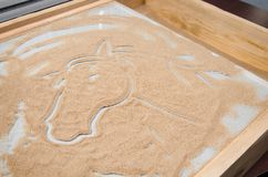 Wooden box with sand and picture of horse. Wooden box with glass for drawing with sand and picture of horse royalty free stock images
