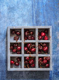 Wooden box with sweet cherry on blue background. Royalty Free Stock Photo